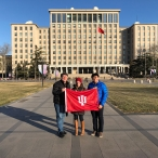 IU Alumni (L-R) Jon Kay, Carrie Hertz, and Peter Yen (IUPUI Recruitment Coordinator and Assistant Office Manager at the China Gateway) pose with the IU Flag on the campus of IU partner Tsinghua University in Beijing. December 8, 2017. Photograph by Jason Jackson.