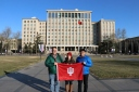 (L-R) Jason Jackson, Carrie Hertz, and Peter Yen pose with the IU Flag on the campus of IU partner Tsinghua University in Beijing. December 8, 2017. Photograph by Jon Kay.