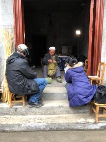 Mr. Li Guicai works on the double-woven lid of his rice basket. Jon Kay (L) Zhang Lijun (R). December 14, 2017. Photograph by Jason Baird Jackson.
