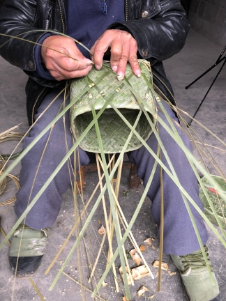 During his second day of work on it, Mr. Li Guicai added the functional and decorative base to the double-woven sticky rice basket with lid. December 15, 2017. Photograph by Jason Baird Jackson.