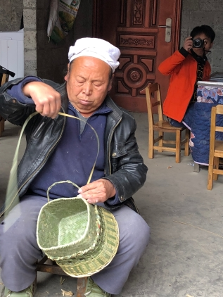 During his second day of work on it, Mr. Li Guicai added the functional and decorative base to the double-woven sticky rice basket with lid. Here the basket gets its first of two bail handles. December 15, 2017. Photograph by Jason Baird Jackson.