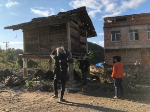 Measuring and photographing a rectangular wood-walled grainery in Manjiang village. Kurt Dewhurst (L), Jon Kay (center, measuring) and Lu Chaoming (R). December 15, 2017. Photograph by Jason Baird Jackson.