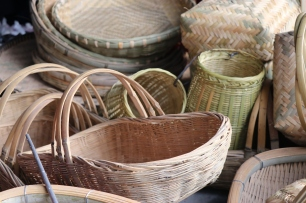"""Baskets for sale on market day in Lihu town at the stall of Li Guozhong. The smaller open mouth baskets tied together are a pail of """"shuttle baskets"""" for use at a loom. December 16, 2017. Photograph by Jon Kay."""