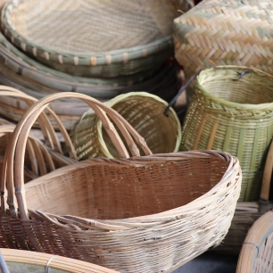 "Baskets for sale on market day in Lihu town at the stall of Li Guozhong. The smaller open mouth baskets tied together are a pail of ""shuttle baskets"" for use at a loom. December 16, 2017. Photograph by Jon Kay."