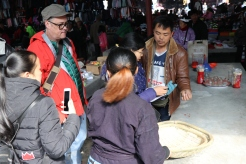 Zhang Lijun asks Li Guozhong about the baskets that he sells at his stand on market day in Lihu town. December 16, 2017. Photograph by Jon Kay.