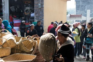 Customers shop for baskets on market day in Lihu town at the stall of Li Guozhong. December 16, 2017. Photograph by Jon Kay.