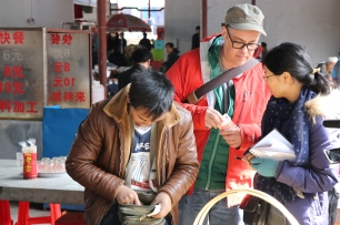 Zhang Lijun (R) and I (C) plan our purchase of baskets from Li Guozhong (L) at his stand on market day in Lihu town. December 16, 2017. Photograph by Jon Kay.