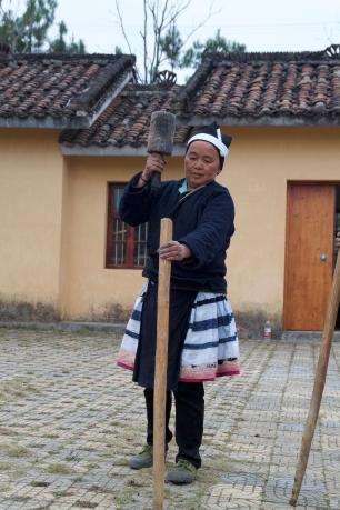A Baiku Yao woman uses a mallet to drive posts used in preparing a loom for weaving. December 17, 2017. Photograph by Carrie Hertz.